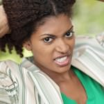 Angry woman holding her curly hair in hands