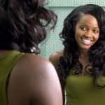Young black woman with long hair looking in mirror
